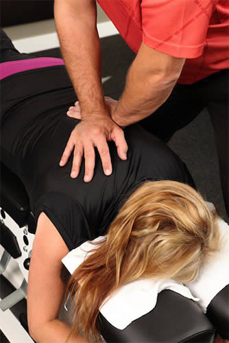 Lady getting a chiropractic adjustment to her back.