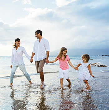 Family that receives chiropractic care enjoying a walk at the beach